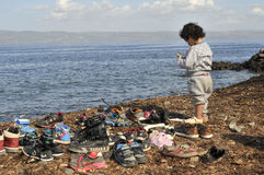 Refugee child at beach Lesvos Greece. Lesvos, Greece- October 12, 2015, 2015. Refugee migrants, arrived on Lesvos in inflatable dinghy boats, they stay in royalty free stock photo