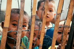 Refugee children behind barbed wire, bamboo fence. Hmong  children from Laos at a refugee camp in Chiang Kham, Payao, Thailand, 1987 Stock Image