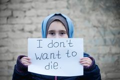 Refugee girl with an inscription on a white sheet. `i dont want to die royalty free stock images