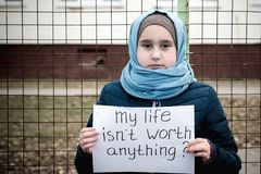 Refugee girl with an inscription on a white sheet. Refugee girl with the inscription on a white sheet ` my life is worth anything royalty free stock photo