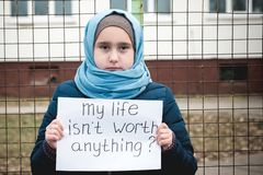 Refugee girl with an inscription on a white sheet royalty free stock images