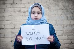Refugee girl with an inscription on a white sheet stock images