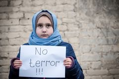 Refugee girl with an inscription on a white sheet royalty free stock photos