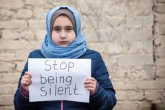 Refugee girl with an inscription on a white sheet royalty free stock image