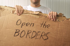 Refugee holding cardboard with Open the borders request Stock Photos