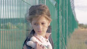 Refugee homeless child. portrait of Caucasian little girl standing in front of metal fence, she is unhappy and resentful.