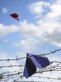 Refugee passport hangs in barbed wire, an European passport flie Stock Images