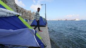 A refugee sits in his tent on the waterfront Aegean sea. KOS, GREECE - FEB 28, 2015: A refugee sits in his tent on the waterfront Aegean sea. Kos island is stock footage