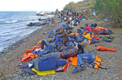 Refugee sleeping on lifejackets at beach Lesvos Greece. Lesvos, Greece-October 25, 2015: Refugee migrants, arrived on Lesvos in inflatable dinghy boats, they stock images