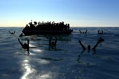 Refugees on a big rubber boat in the middle of the sea that require help. Sea with people in the water asking for help. Migrants crossing the sea stock illustration