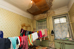 Refugees` clothes is drying of on the rope in the temporary apartment with damaged ceiling.  Royalty Free Stock Images