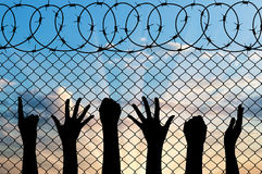 Refugees hands silhouette near the fence of barbed wire. Refugee concept Stock Photography