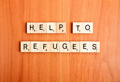 Refugees help text wooden tiles letters. Refugees help text on wooden tiles letters royalty free stock image
