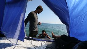 Refugees in his tent on the waterfront Aegean sea. stock footage