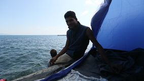 Refugees in his tent on the waterfront Aegean sea. Many refugees come from Turkey in an inflatable boats. KOS, GREECE - FEB 28, 2015: Refugees in his tent on stock video