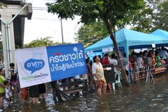 Refugees are queuing to pick up a free meal in a flooded street of Bangkok, Thailand, on 31 October 2011.  Royalty Free Stock Photography