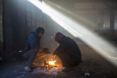 Refugees try to warm in an abandoned hangar. Belgrade, Serbia - January 7, 2017: Refugees try to warm in an abandoned hangar near the main train station. The Stock Photo