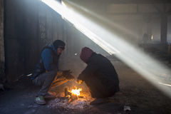 Refugees try to warm by the fire in an abandoned hangar Royalty Free Stock Photography