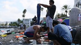 Refugees wash clothes on the beach.  Many refugees come from Turkey in an inflatable boats. stock video