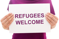 Refugees welcome. Girl holding white paper sheet with text Refugees welcome stock images