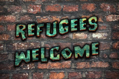 Refugees Welcome Graffiti. Refugees Welcome slogan written in graffiti on grunge brick wall Royalty Free Stock Photos