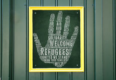 Refugees Welcome. Slogan written in chalk on blackboard and other related words in help hand shape Stock Images