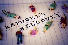 Refugees welcome text on paper. Refugees welcome text on white line paper with woman figures around Royalty Free Stock Image