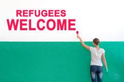Refugees welcome. On the white wall with paint write Refugees welcome stock photography
