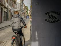 Refugees Welcome - Porto - Portugal. A woman riding past a political message - Porto - Portugal stock photos