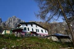 Refugio 'Alpinisti Monzesi 'en un día soleado caliente de la primavera con un disco del sol en fondo y los paneles solares fotos de archivo libres de regalías