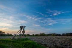 Refugio de la caza al lado del campo marrón durante puesta del sol Foto de archivo libre de regalías
