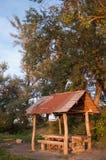Refugio de madera en el bosque en la puesta del sol Foto de archivo libre de regalías