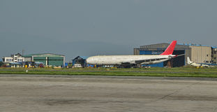 Refurbished airline in front of hangar building at Nepal Tribhuvan International Airport Royalty Free Stock Photos