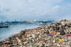 Refuse area near harbor view full of smoke, litter, plastic bottles,rubbish and trash at the Thilafushi local tropical island. Refuse area near harbor view full Royalty Free Stock Photo