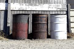 Refuse Barrels. Old rusty metal trash containers sit behind a wooden fence Stock Photos