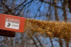 Refuse blows through a wood shredder. A wood shredder blows refuse into a trailer at a high speed where a sign reads DANGER of FLYING MATERIAL Royalty Free Stock Image