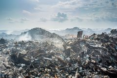 Refuse at the garbage dump with lot of smoke, litter, plastic bottles,rubbish and trash at tropical island stock images