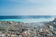 Refuse at the garbage dump near the beach full of smoke, litter, plastic bottles,rubbish and trash at tropical island. Refuse at the garbage dump near the beach Stock Images