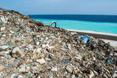 Refuse at the garbage dump near the ocean full of smoke, litter, plastic bottles,rubbish and trash at tropical island. Refuse at the garbage dump near the ocean Royalty Free Stock Photos