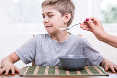 Refusing to eat disgusting food. Picky eater boy refusing to eat disgusting food stock photo