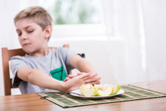 Refusing to eat healthy food. Little kid refusing to eat healthy food stock photo