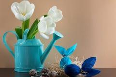 Regadera azul con los tulipanes blancos y dos huevos de Pascua en la forma de conejo en fondo marrón Adornamiento del día de fies Fotos de archivo libres de regalías