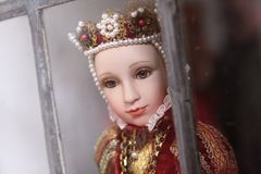 Regal doll. Regal queen or princess doll toy looking through metal bars Royalty Free Stock Photo