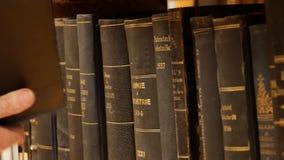 Regal mit Büchern - suchen Sie das Buch in den Regalen stock video footage