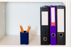 Regal mit Büroordnern und Bleistifthalter Lizenzfreie Stockfotos