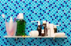 Regal mit Toilettenartikelkosmetik auf Hintergrundbadezimmer lizenzfreies stockbild