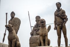Oba Of Benin. Regal Statue of The Oba of Benin. The king is flanked by two guards and two guard dogs royalty free stock photo