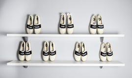 Regale voll von weißen Schuhen im grauen Hintergrund Lizenzfreies Stockfoto