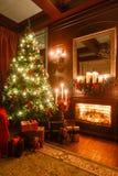 Regali all'albero di Natale Natale che anche dal lume di candela appartamenti classici con un camino immagine stock libera da diritti
