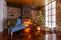 Regali all'albero di Natale Natale che anche dal lume di candela appartamenti classici con un camino immagine stock